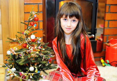 Child girl in red dress by a fireplace on Christmas Stock Photo - 25824745