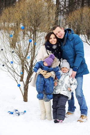 Portrait of happy family enjoying beautiful winter day outdoors photo