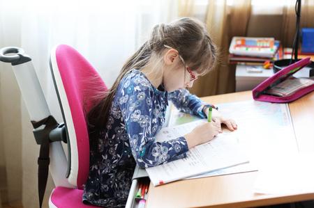 Little girl writing her homework at the desk in her room photo