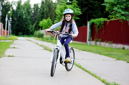 niños en bicicleta: Retrato de una muchacha del niño en una bicicleta en el día de verano al aire libre Foto de archivo