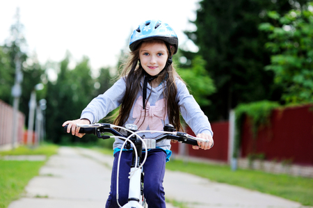 ni�os en bicicleta: Retrato de una muchacha del ni�o en una bicicleta en el d�a de verano al aire libre Foto de archivo