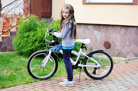 tween: Portrait of a child girl with a bicycle on summer day outdoors