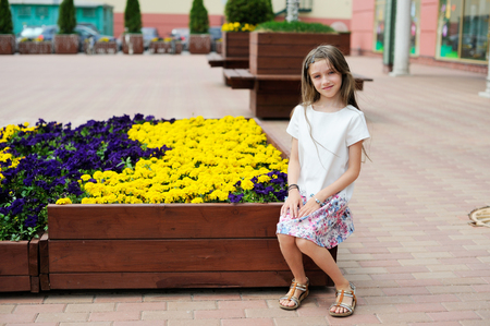 Stylish brunette kid girl sitting on bench on shopping city street photo