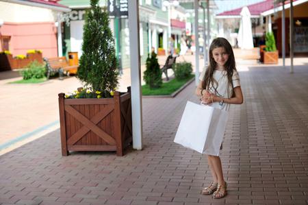 tween: Stylish brunette kid girl walking along the shopping city street