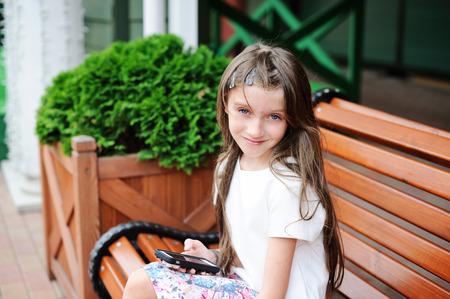 tween: Stylish brunette kid girl sitting on bench on shopping city street