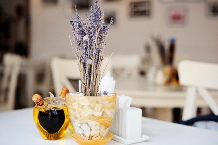 statics: White table in the restaurant with lavender in pot and olive oil