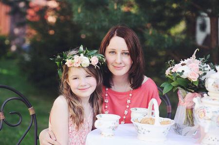 mama e hija: Retrato de la madre joven y su hija llevaba corona de flores sentado en la mesa de t� al aire libre