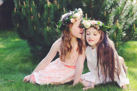 Two kid girls in elegant dresses with floral wreath on heads sitting on the lawn and speaking Stock Photo