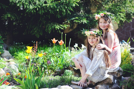 tween: Two kid girls in elegant dresses with floral wreath on heads sitting by pool