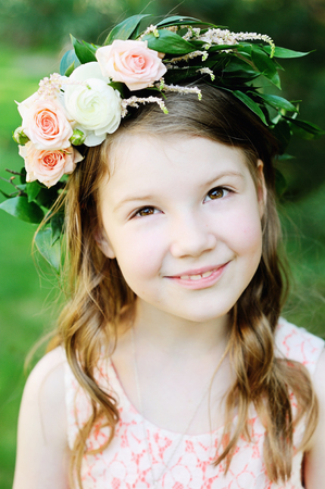 Outdoor portrait of adorable kid girl with floral wreath in garden photo