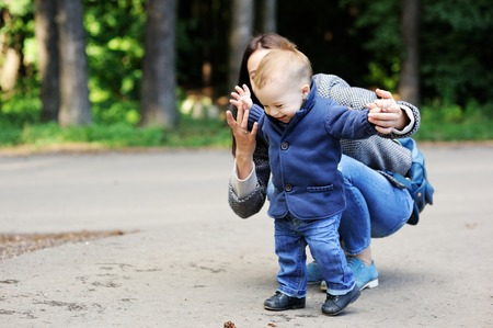 niños caminando: Madre feliz que recorre con su bebé en el parque Foto de archivo