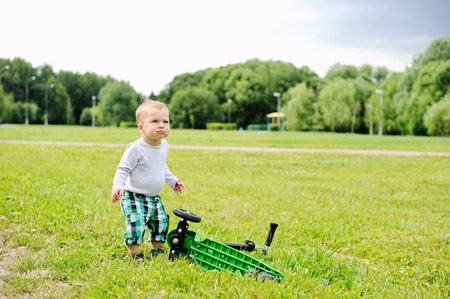 Portrait of adorable blond baby boy walking in park photo