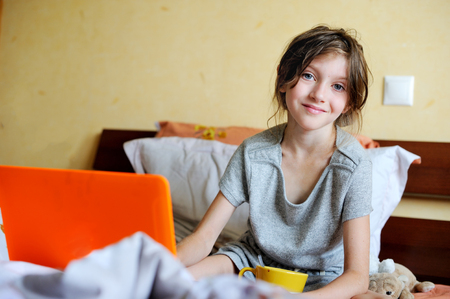 Smiling young teenager lying on her bed and using a laptop