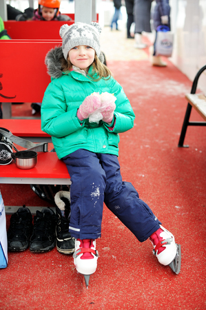 bobble: Adorable little girl in winter clothes and bobble hat skating on ice rink Stock Photo