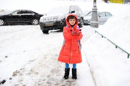 Adorable little girl walking from school on winter day in the city