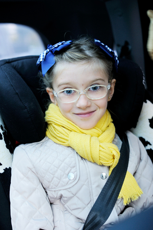 school aged: Beauty school aged kid girl in glasses and yellow scarf in the car seat with belt Stock Photo