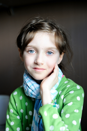 brunette girl: Portrait of  beauty kid girl in the blue scarf indoor