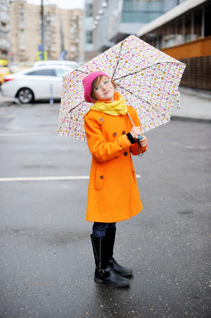 girl boots: Adorable, elegant school aged kid  girl wearing orange  coat, yellow scarf and pink hat, and boots holding colorful umbrella walking in the city street autumn  day