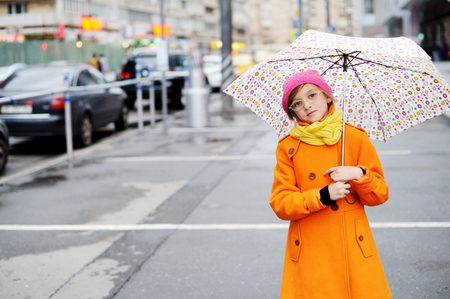 pink hat: Adorable, elegant school aged kid  girl wearing orange  coat, yellow scarf and pink hat, and boots holding colorful umbrella walking in the city street autumn  day