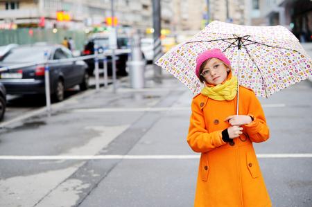 Adorable, envejecido muchacha niño elegante escuela con capa de color naranja, amarillo y bufanda sombrero de color rosa y botas con colorido paraguas caminando en la calle de la ciudad el día de otoño Foto de archivo - 55705276