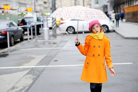 school aged: Adorable, elegant school aged kid  girl wearing orange  coat, yellow scarf and pink hat, and boots holding colorful umbrella walking in the city street autumn  day