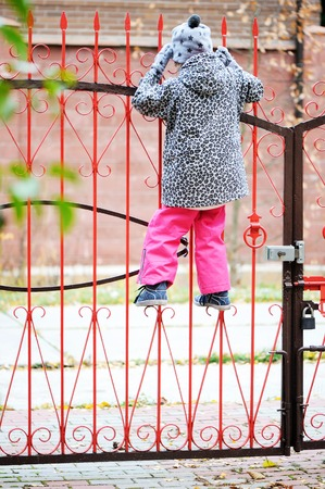 climbed: happy cute Kid girl  climbed on a red fence from her house