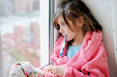 gir: Ill child gir in cozy pink robel sitting near the window and holding thermometer