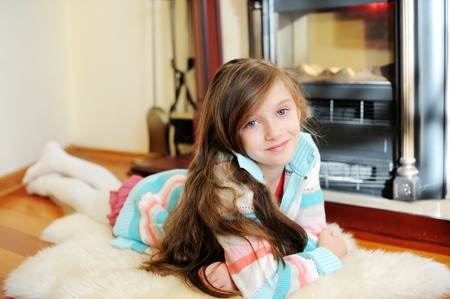 baby open present: Adorable kid girl in in cozy warm sweater near fireplace Stock Photo