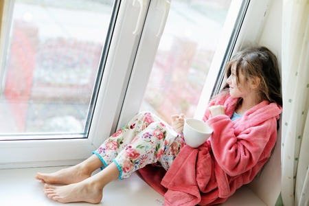 small girl: Beautiful little girl in cozy pink bathrobe drinking tea from white  cup on the window