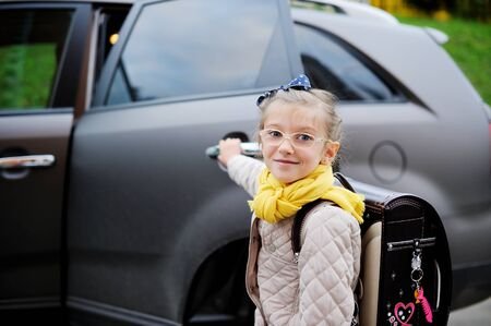 school aged: Beauty school aged kid girl in glasses and yellow scarf inear the car