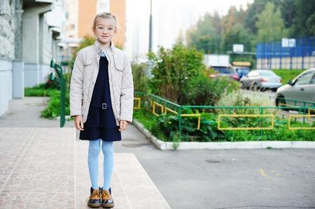 uniformes: Niña de la escuela en uniforme azul marino en su camino a la escuela en la ciudad