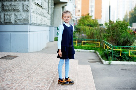 children clothing: School girl in navy blue uniform on her way to school in the city