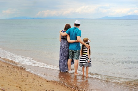 wet dress: Happy young family having fun on the beach Stock Photo