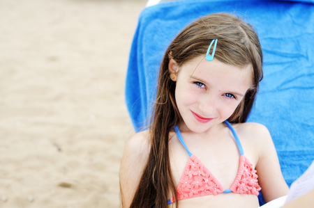 Adorable beautiful brunette kid  girl having fun on the beach Reklamní fotografie