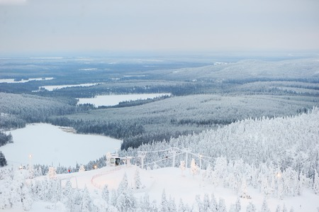 Beautiful view of finnish landscape with trees in snow, ruka, karelia, lapland, hilly winter landscapes in famous winter sports area called Ruka photo