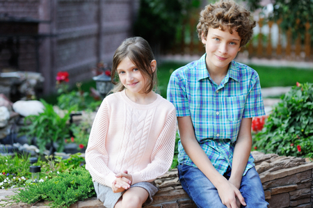 little  girls: Adorable preteen boy and girl in the garden Stock Photo