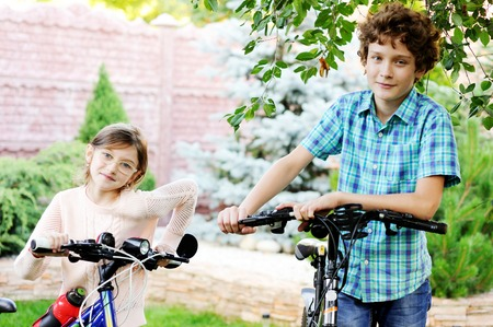 school aged: Adorable school aged boy and girl in the garden with bikes Stock Photo