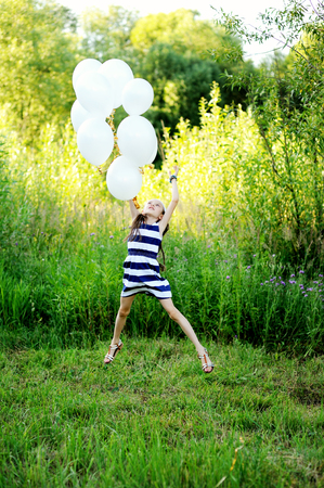 kids outside: Active kid girl in stripe dress has fun with white balloons outdoor on the beauty summer day: runs and jumps Stock Photo