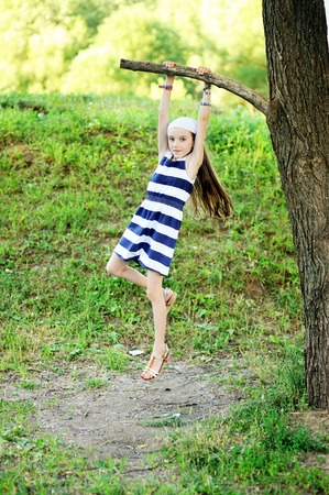 tween: Active kid girl in stripe dress has fun with white balloons outdoor on the beauty summer day: runs and jumps Stock Photo