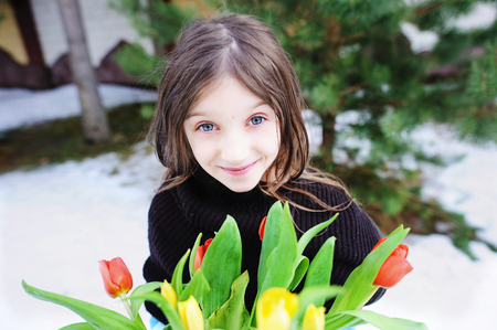 snow flowers: Close up spring portrait of brunette child girl with bouquet of tulips on the walk in the beauty early spring day Stock Photo