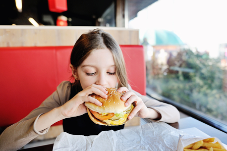 fast food restaurant: Cute little girl in school uniform eating a hamburger and potatos in the restaurant Stock Photo