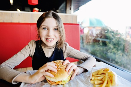 niños comiendo: Niña linda en uniforme escolar comer una hamburguesa y patatas en el restaurante Foto de archivo