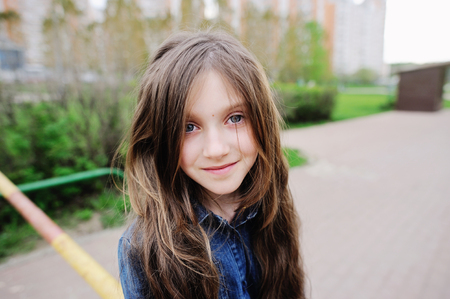 brunette girl: Portrait of brunette kid girl in fashion outfit outdoor in the park