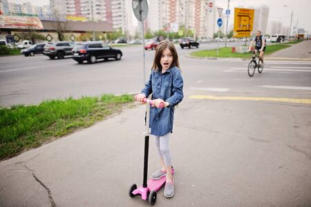 school aged: School aged little girl in dress on the scooter in the city street Stock Photo