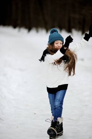 neve palle: Funny little girl having fun in beautiful winter park with snowballs
