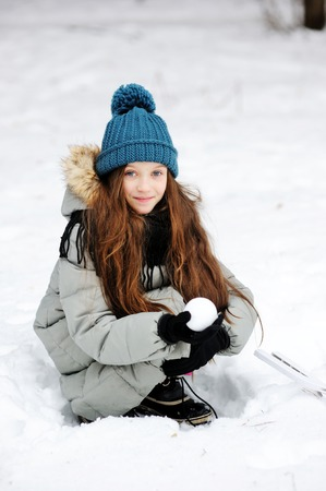 palle di neve: Funny little girl having fun in beautiful winter park with snowballs