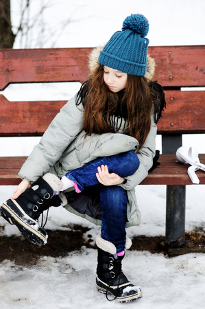 girl boots: Funny little girl having fun in beautiful winter park and put off snow from the boots Stock Photo
