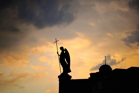 patron of europe: Silhouette of monument with angel on the top of it at sunset. Brest, Belarus Stock Photo