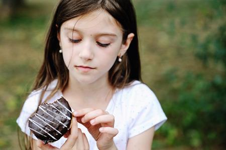 niña comiendo: Cute kid girl eating sweet donut outdoor in the park on sunny warm day. Focus on donut