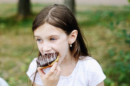 niña comiendo: Muchacha linda del cabrito que come el buñuelo dulce al aire libre en el parque el día cálido y soleado Foto de archivo